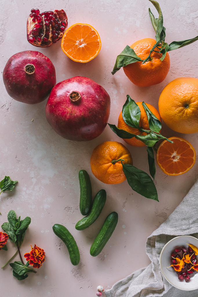 pomegranates, mandarin oranges, mint and nano cucumbers on a pink speckled stone surface