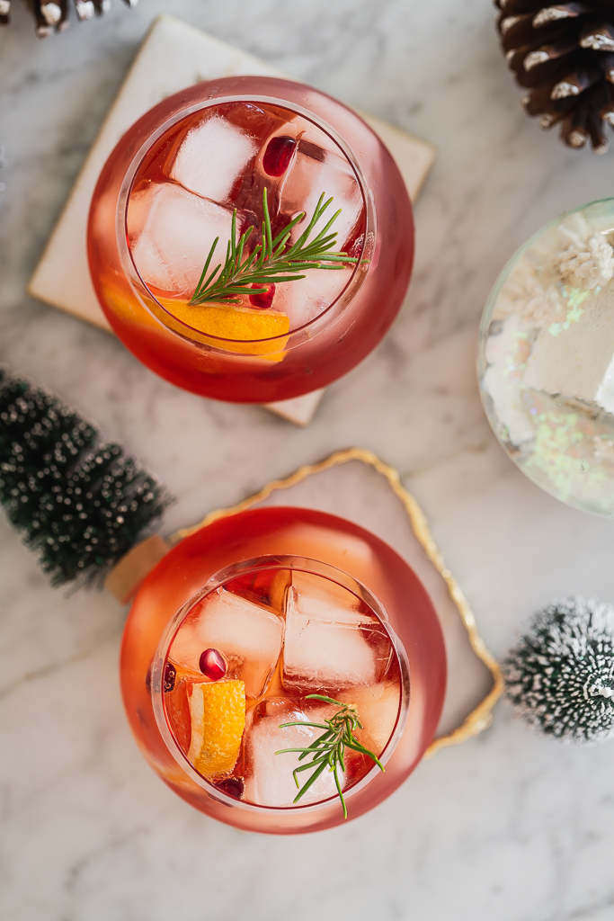 Overhead view of winter cocktails served over ice with pomegranate seeds and a rosemary sprig