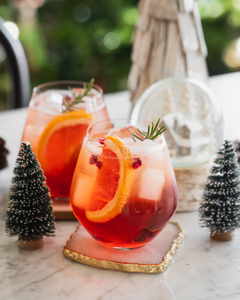 Winter aperol spritz cocktails served in stemless wine glasses with a grapefruit wedge and rosemary sprig