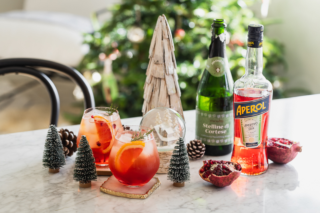a pair of Aperol Spritz cocktails on a marble table with winter decor
