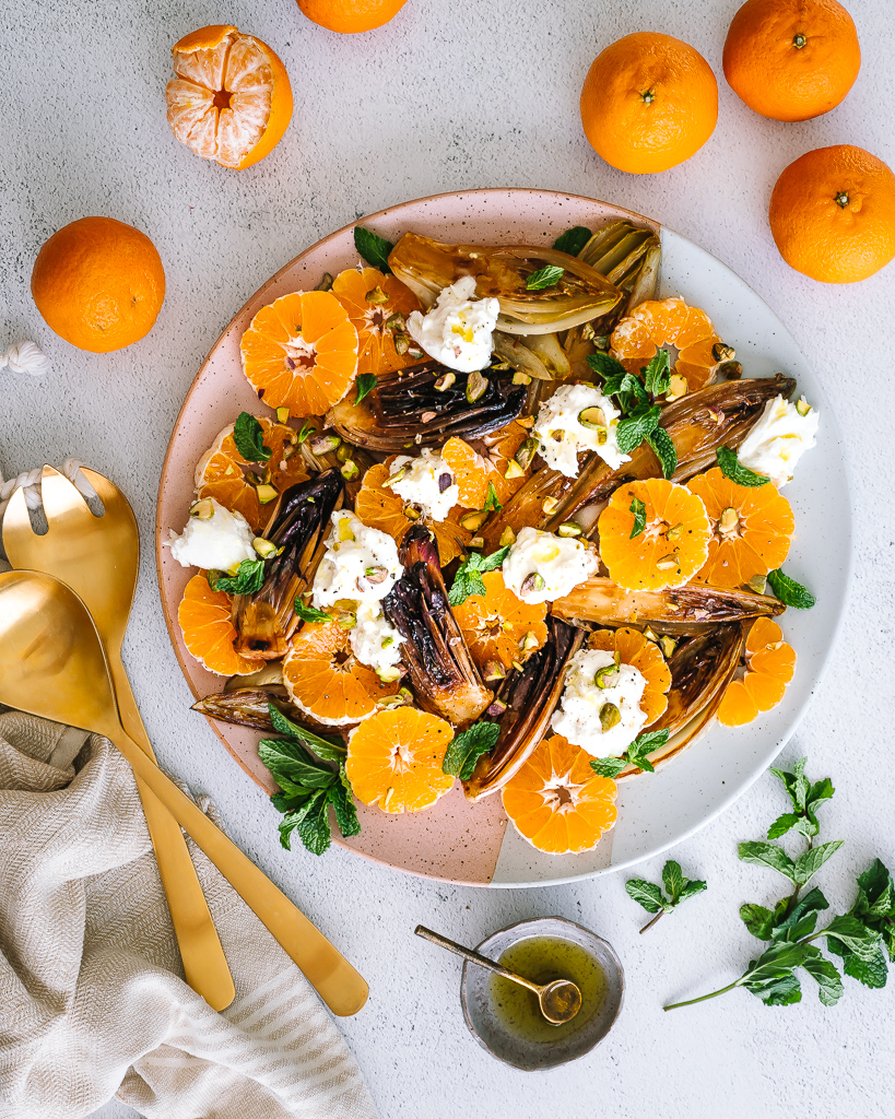 overhead shot of a platter with tangerine slices, burrata and caramelized endive hearts
