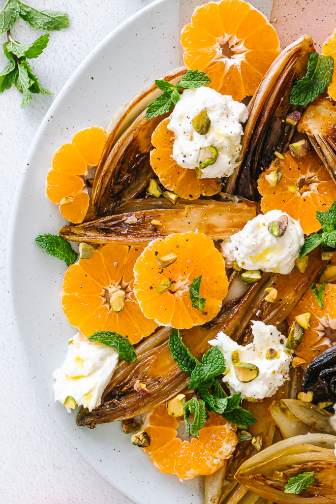 close-up of a platter with caramelized endive hearts, clementines ., mint leaves and chunks of burrata cheese