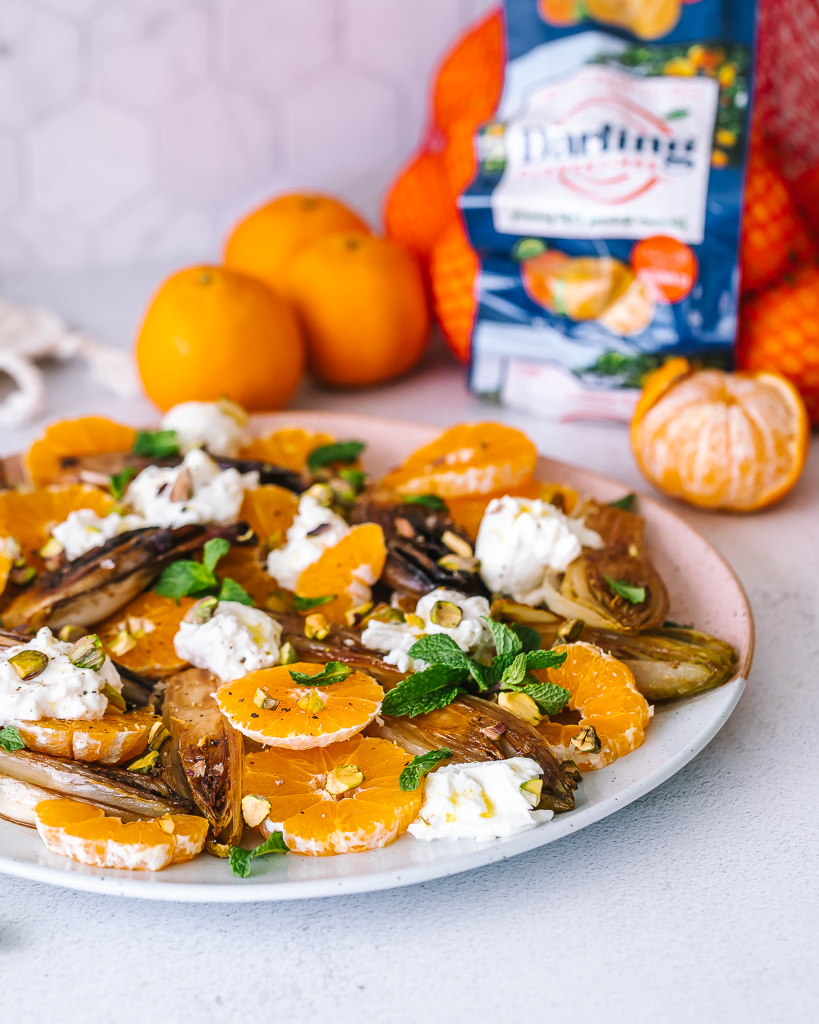 side view of a plate of a caramelized endive salad with fresh sliced clementines and chunks of burrata cheese