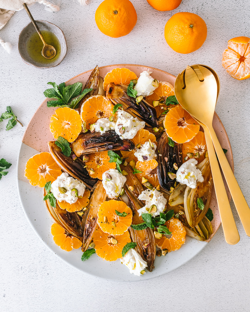 overhead shot of a caramelized endive salad with slices clementines and chunks of burrata cheese