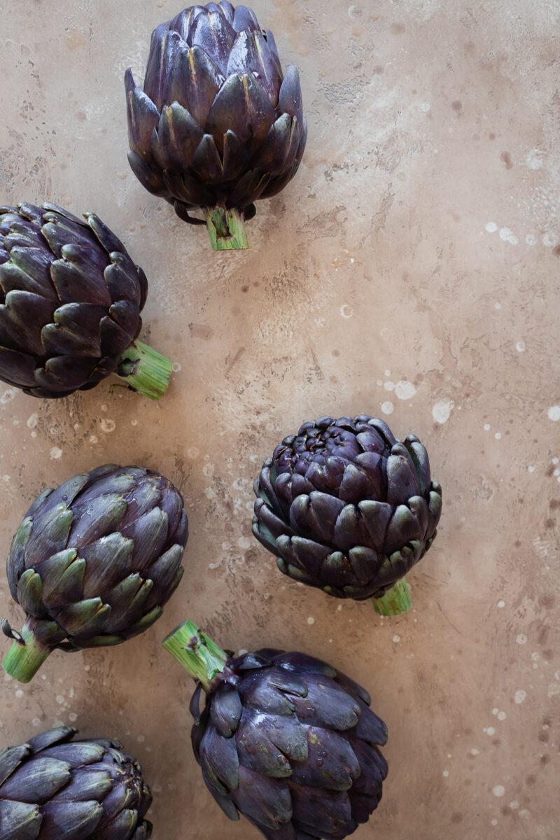Purple artichokes on a beige stone surface.