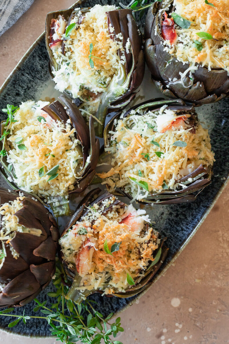 Crab and spinach stuffed artichokes on a blue platter.