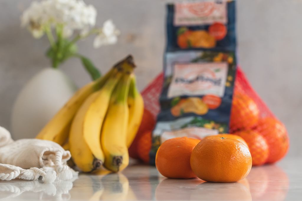 clementines and bananas on a marble countertop