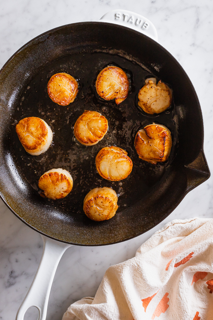 Pan-seared sea scallops in a white Staub cast iron skillet.