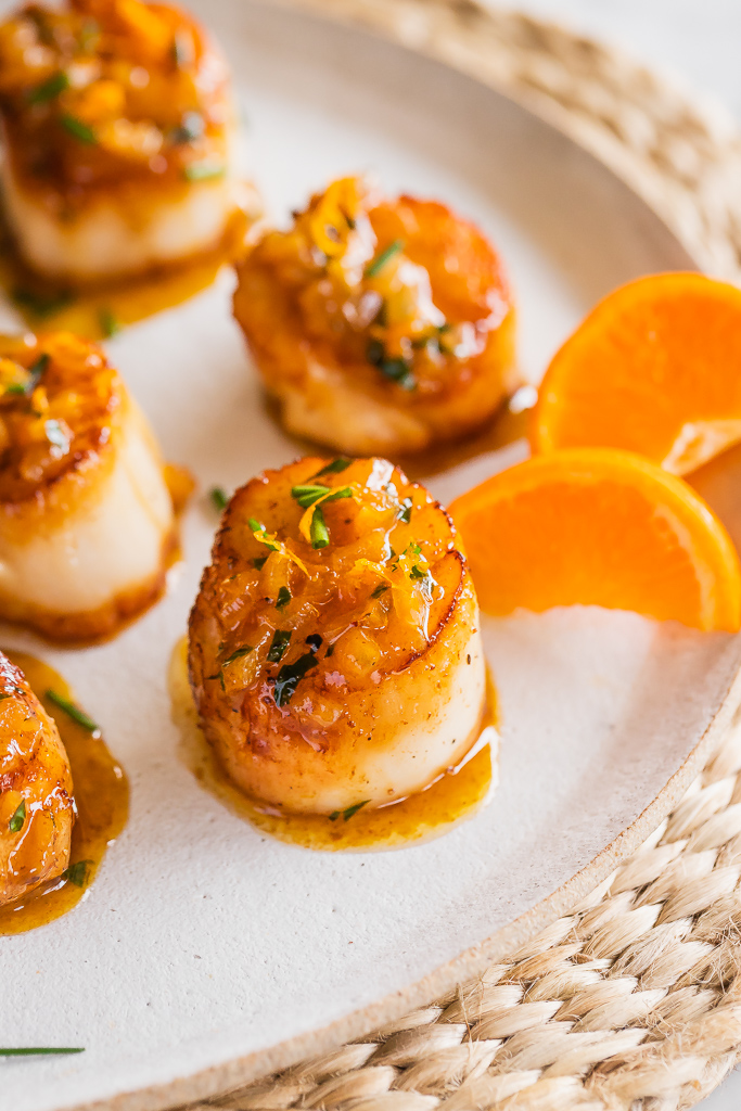 Close up of a seared sea scallop with citrus sauce