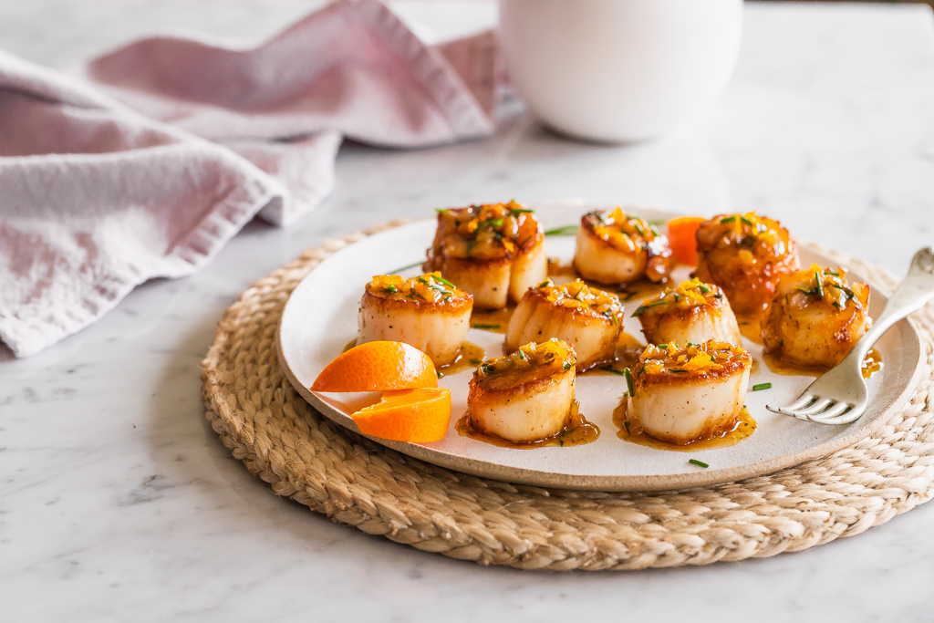 Scallops with citrus butter on a white plate with a silver fork and a woven placemat on a marble table.