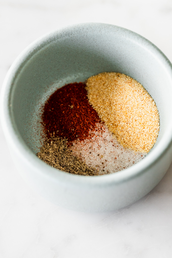 A small, light blue ceramic bowl filled with salt, black pepper, smoked paprika and garlic powder.