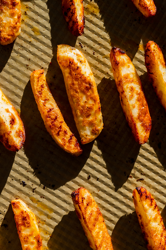 Crispy golden potato wedges on a gold baking sheet.