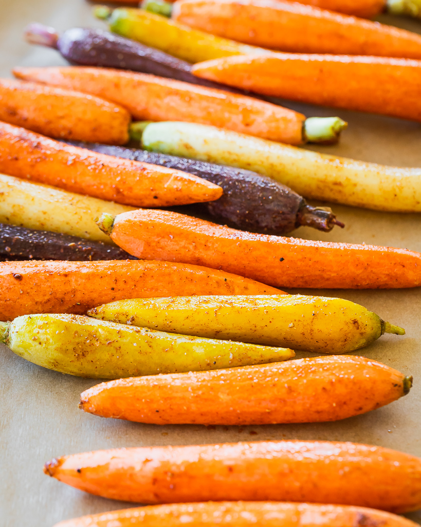 yellow, purple and orange carrots glazed with oil and tossed with Moroccan spices on a lined sheet pan