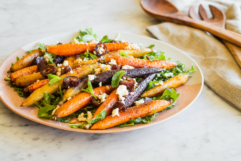 side view of a plate of moroccan roasted carrot salad with chopped dates and crumbled feta served with wooden spoons on the side
