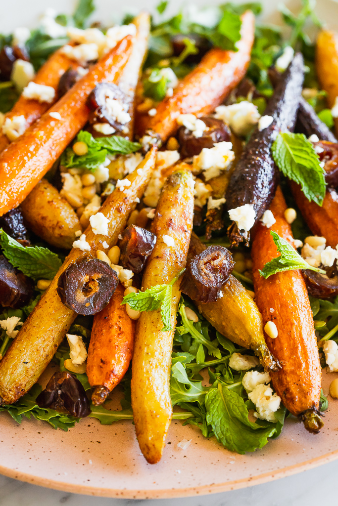 Close-up of of roasted whole carrot salad on a bed of arugula topped with chopped dates and crumbled feta