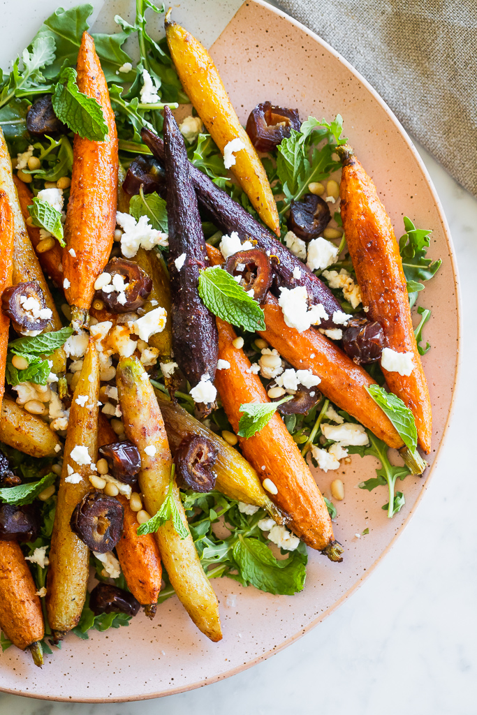 close-up of a platter with moroccan carrot salad with chopped dates and crumbled feta