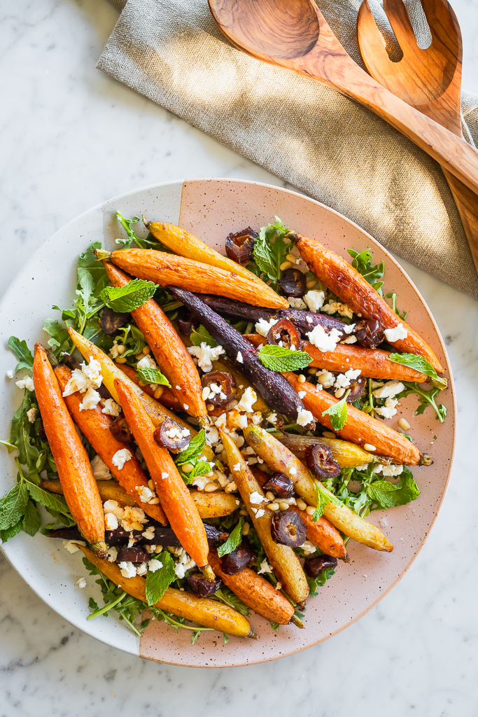 overhead shot of moroccan carrot salad with chopped dates and crumbled feta served with wooden spoons on the side