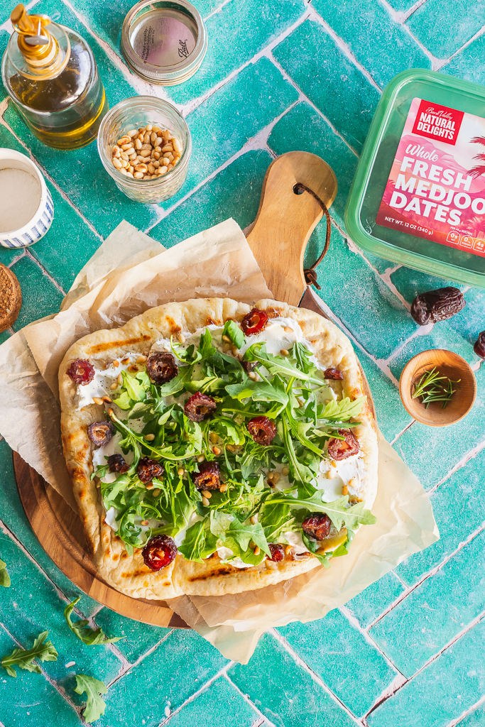 overhead view of a whole date and goat cheese flatbread with surrounding ingredients on a green tile surface