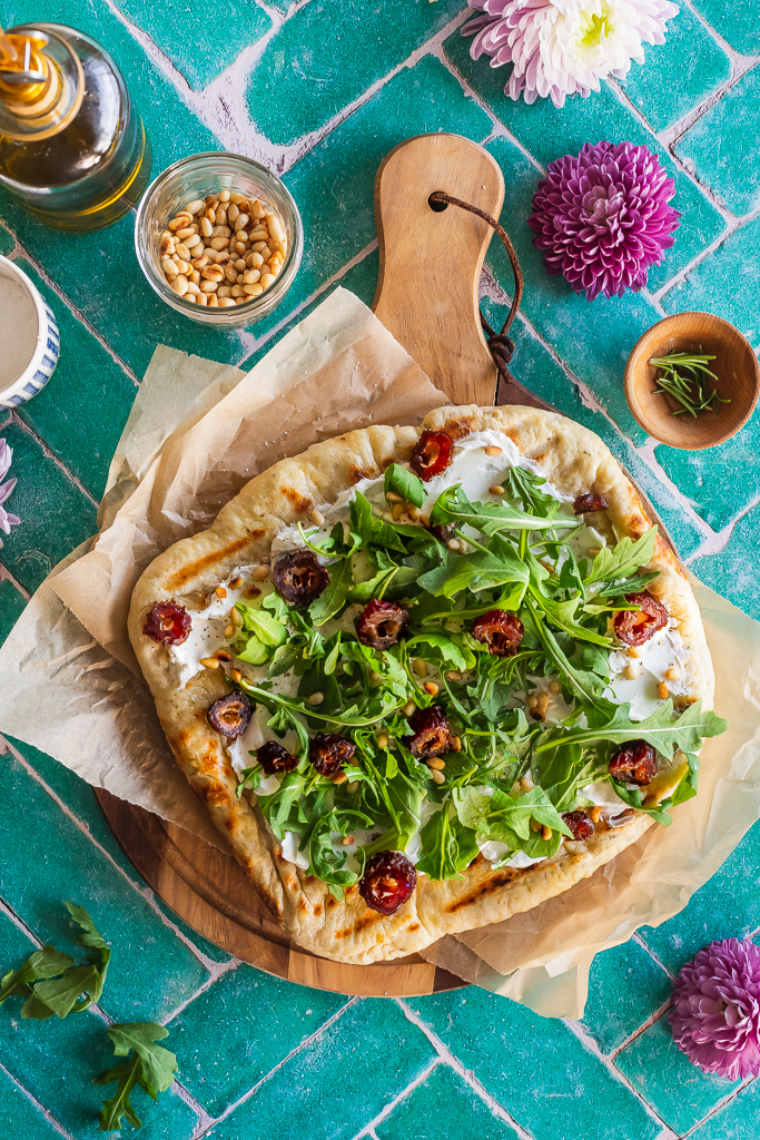 a whole grilled date and goat cheese flatbread with arugula and pine nuts on a round wooden board