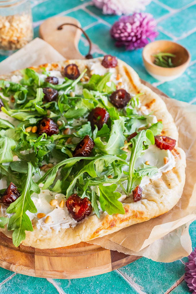 grilled flatbread with goat cheese, dates, arugula and pine nuts on a round wooden board