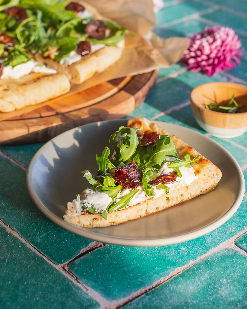 a slice of date and goat cheese flatbread with arugula on a small blue plate with the full flatbread on a wooden cutting bard in the background